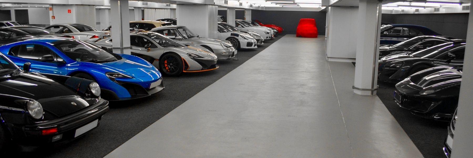 Oldtimer, Sportwagen und Luxusautos parken in einer Halle