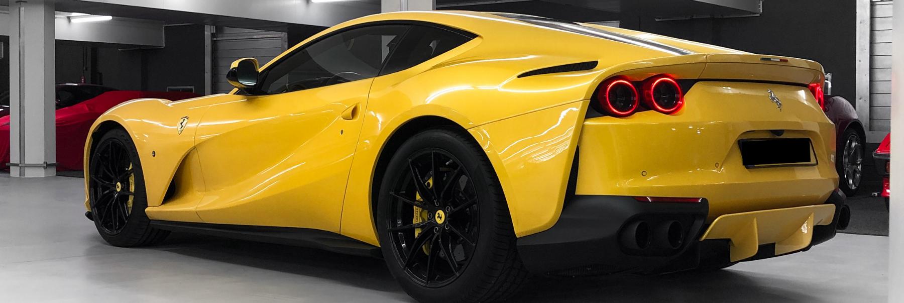 Ferrari 812 Superfast gelb dreiviertel Rückansicht eingelagert in Luxusgarage